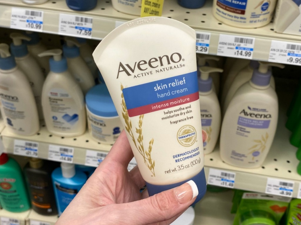 Hand holding a tube of Aveeno brand hand cream near in-store display