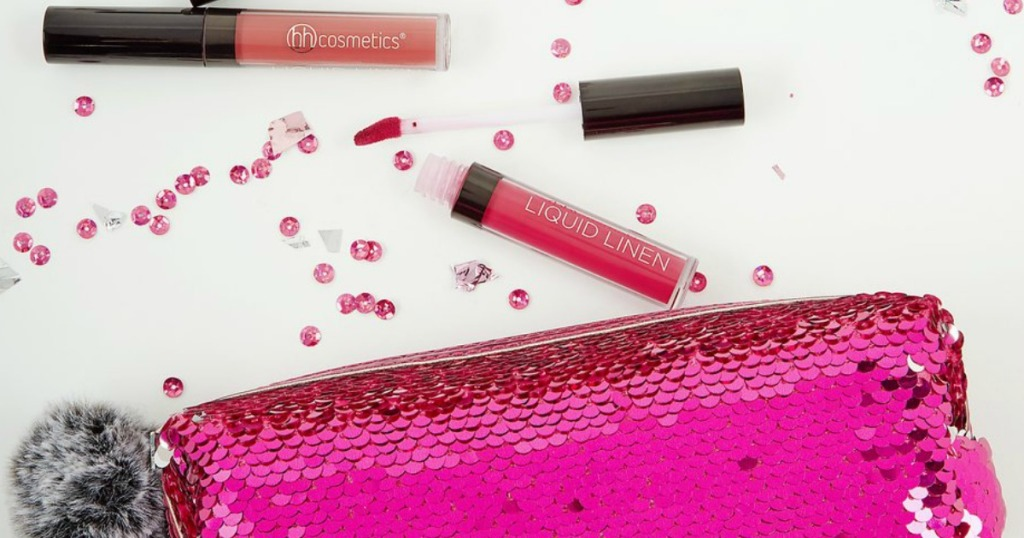lip gloss with confetti around it by a cosmetic bag