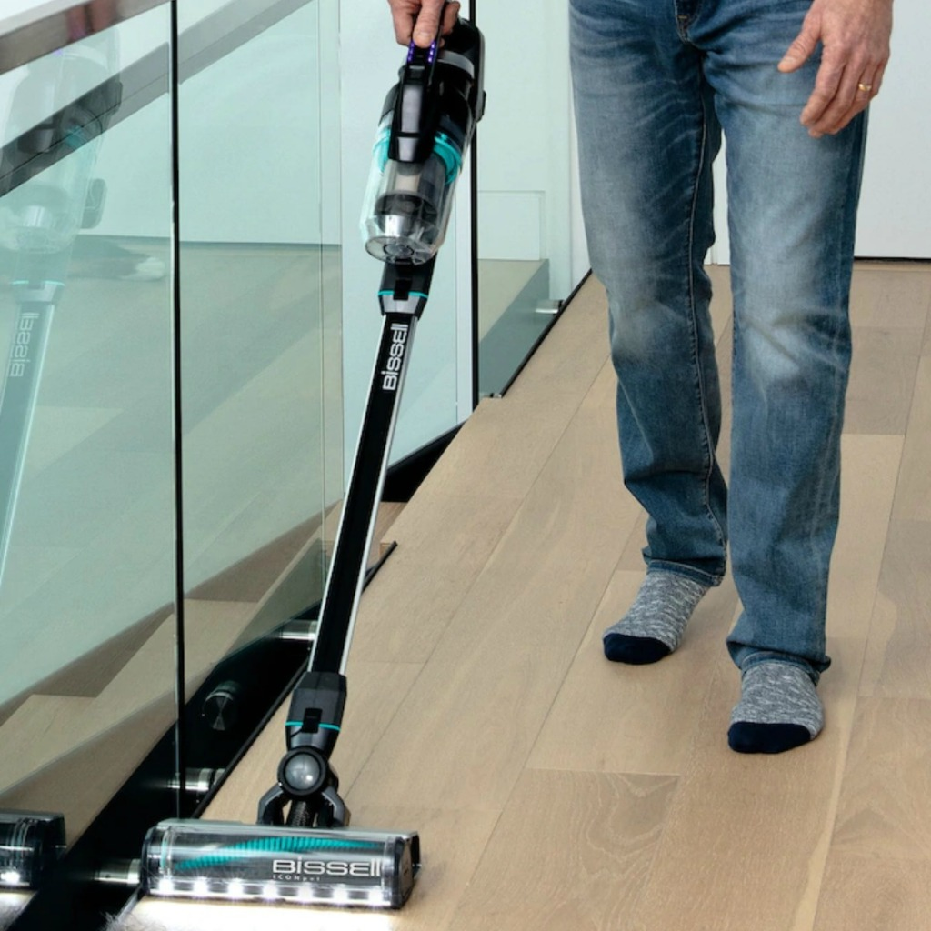 Many using a cordless vacuum on top level with hardwood flooring