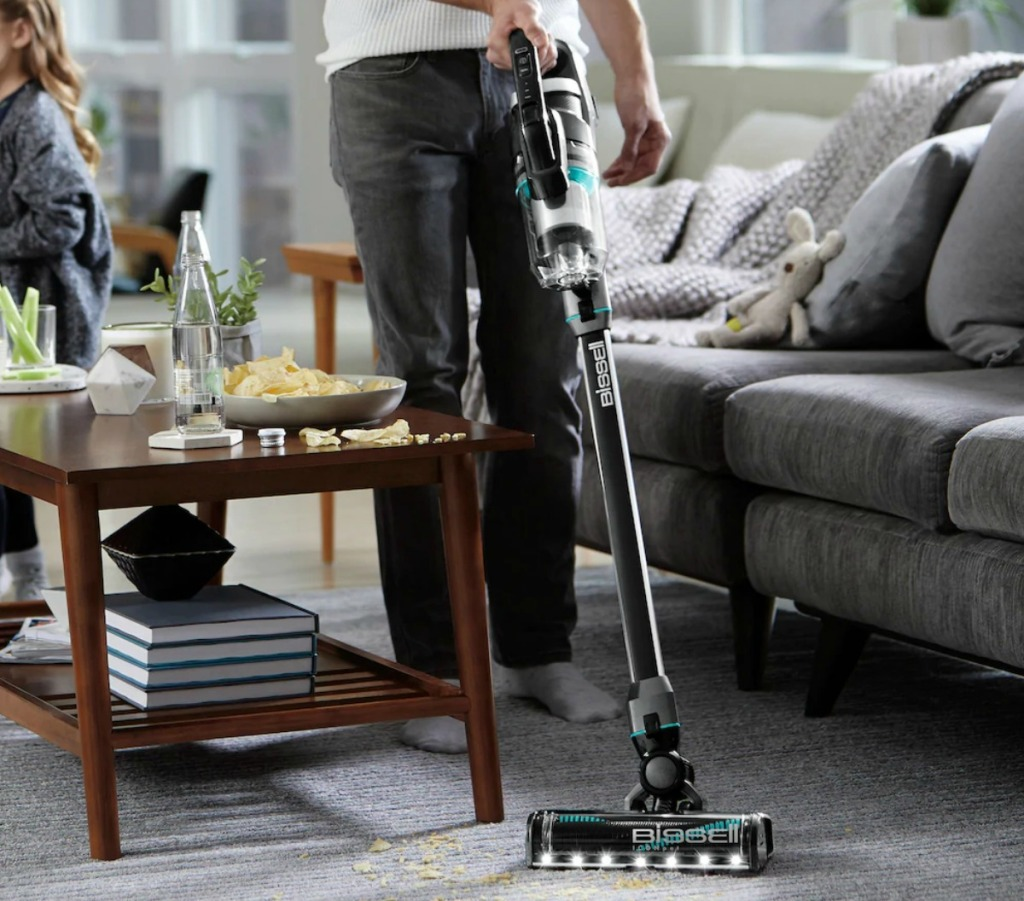 Man using a cordless vacuum to clean crumbs of a carpeted area