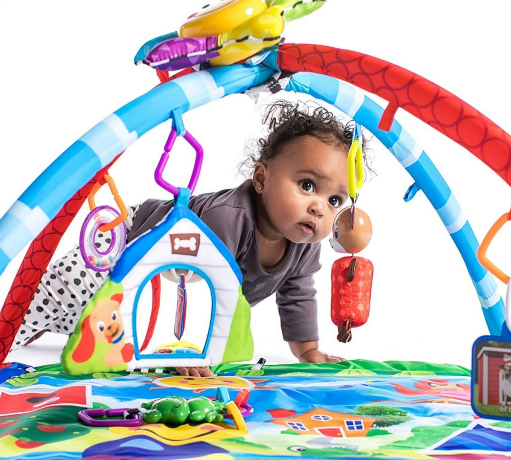 baby crawling through a colorful play gym