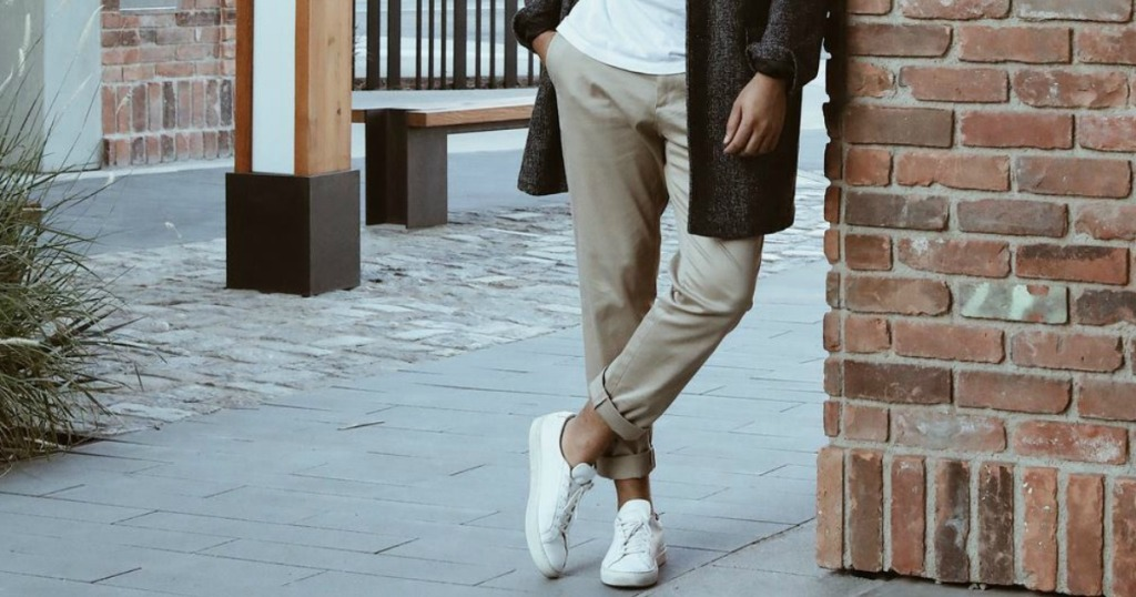 man leaning against a wall wearing khakis