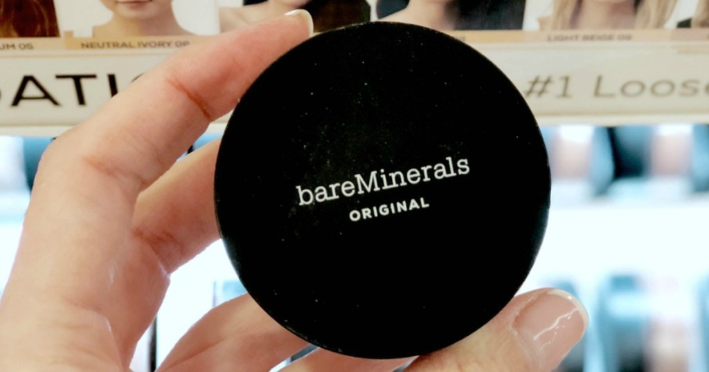 Woman's hand holding a round container of mineral foundation