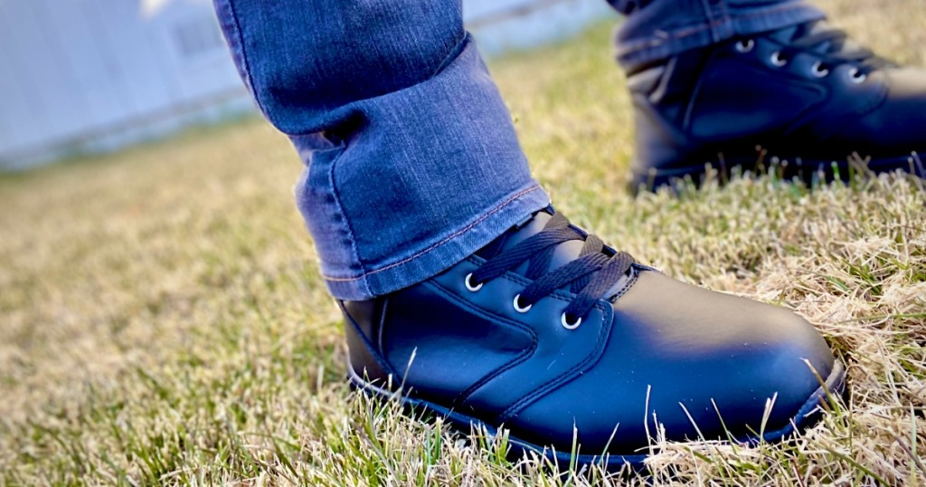 person wearing boots while standing on grass