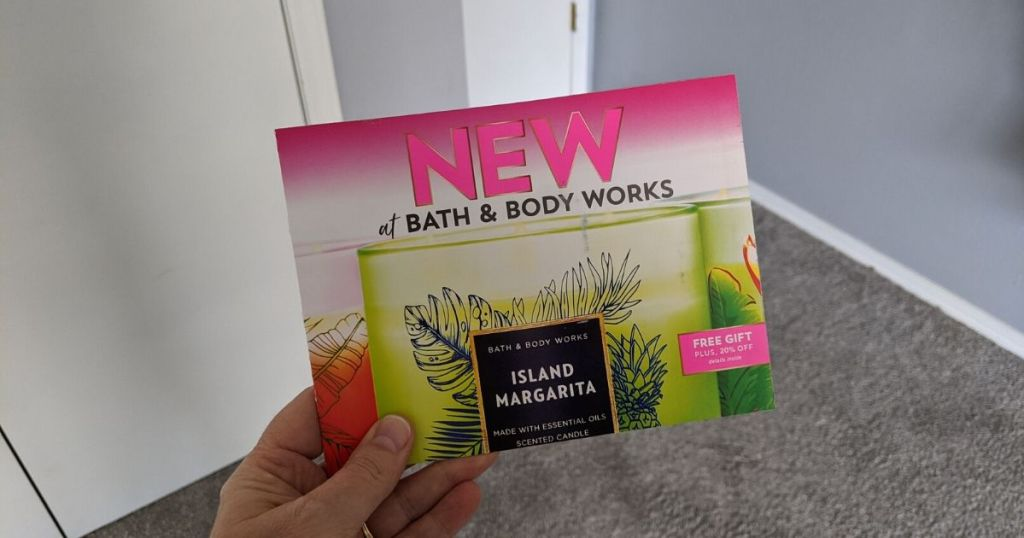 woman's hand holding bath body works mailer with coupons inside