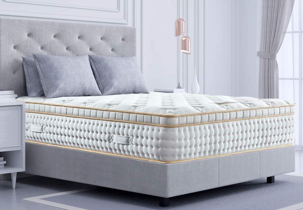 white mattress on bedframe with pillows on it