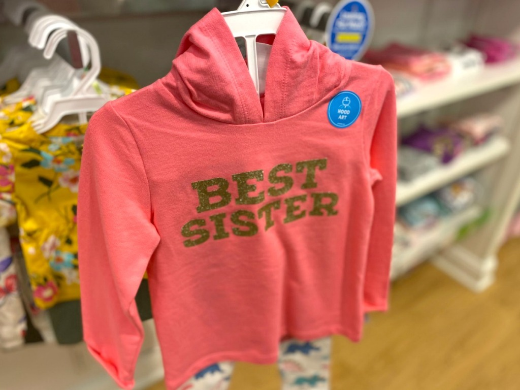 """Pink shirt that says """"Best Sister"""" in gold on hanger"""