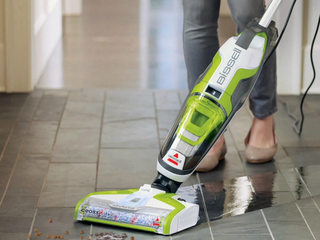 All-in-one style floor cleaning vacuum in green and black on a hardwood surface