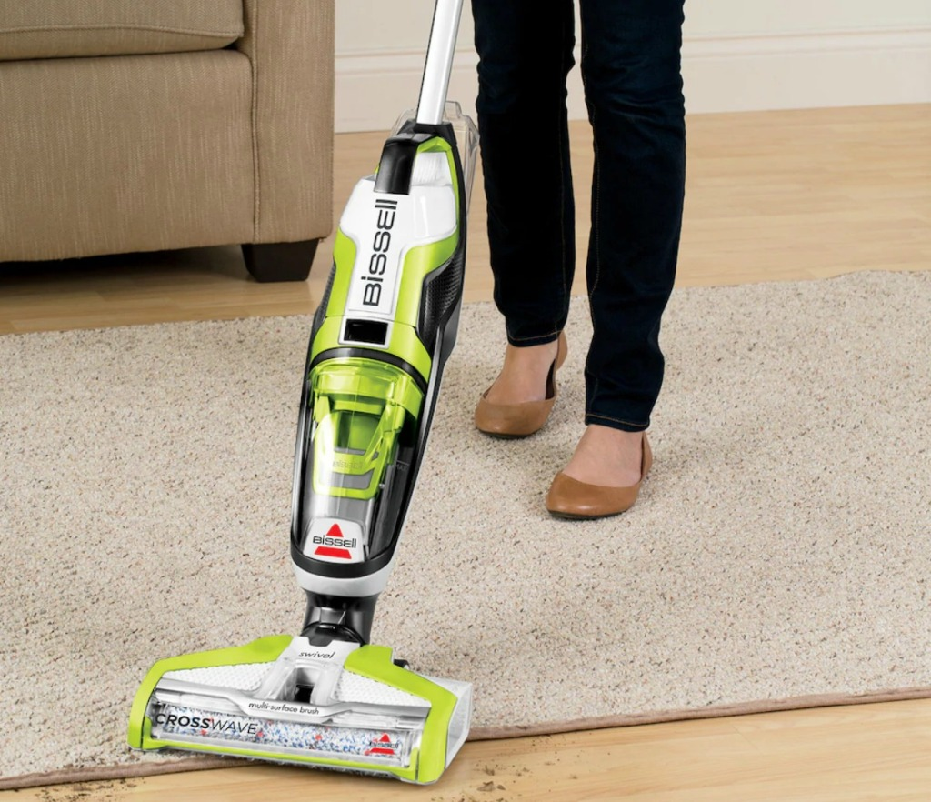 Woman using a green and white all-in-one vacuum cleaner on hardwood floors