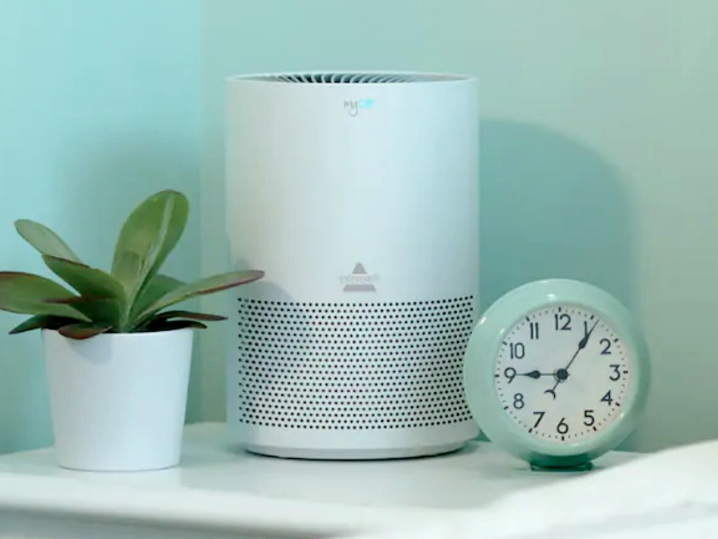 Personal sized air purifier on an end table near a plant and alarm clock