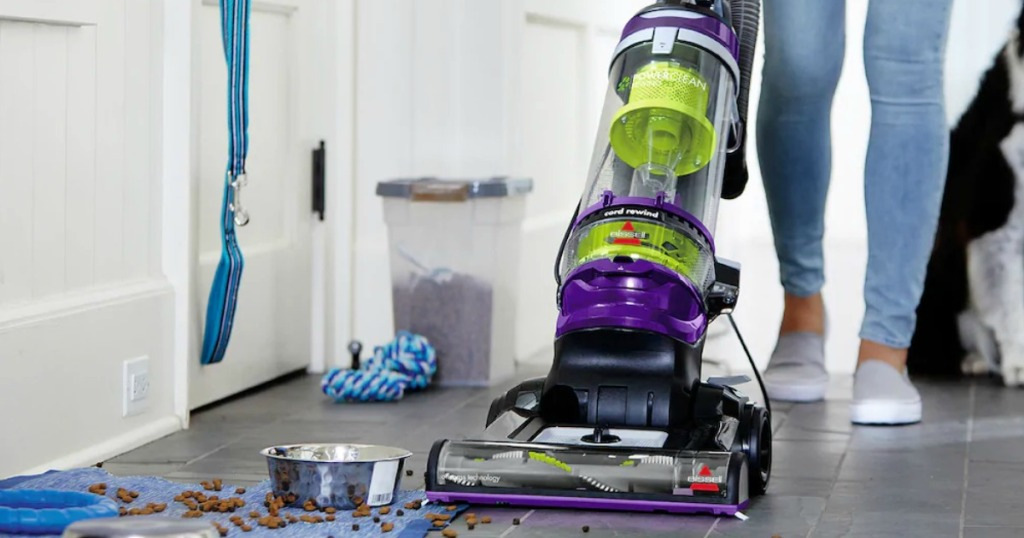 Woman using a large vacuum cleaner on hardwood floor near spilled dog food