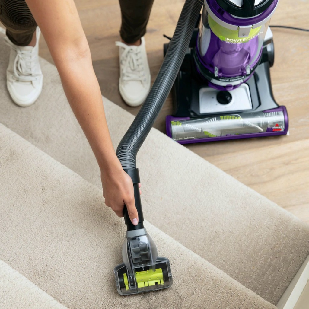 Woman using a vacuum attachment to clean carpeted stairs