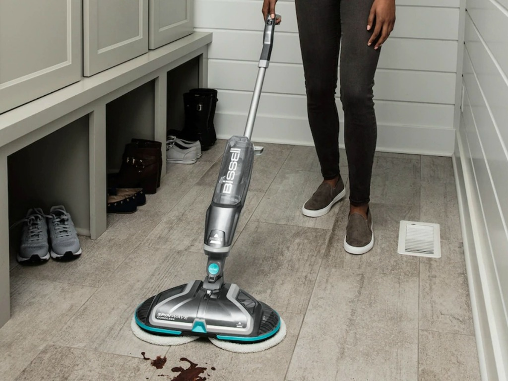 Woman using a Bissell SpinWave cordless mop on hardwood flooring
