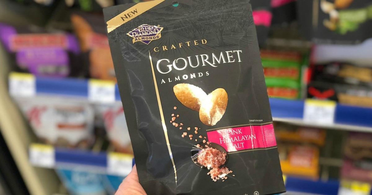 hand holding bag of blue diamond gournet almonds in pink Himalayan salt