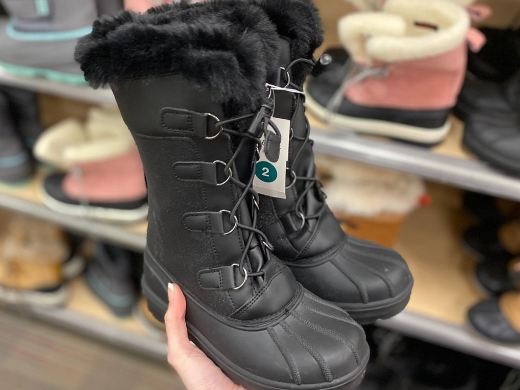 Hand holding little girls black boots at Target