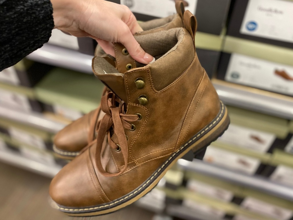 Hand holding men's boots at target
