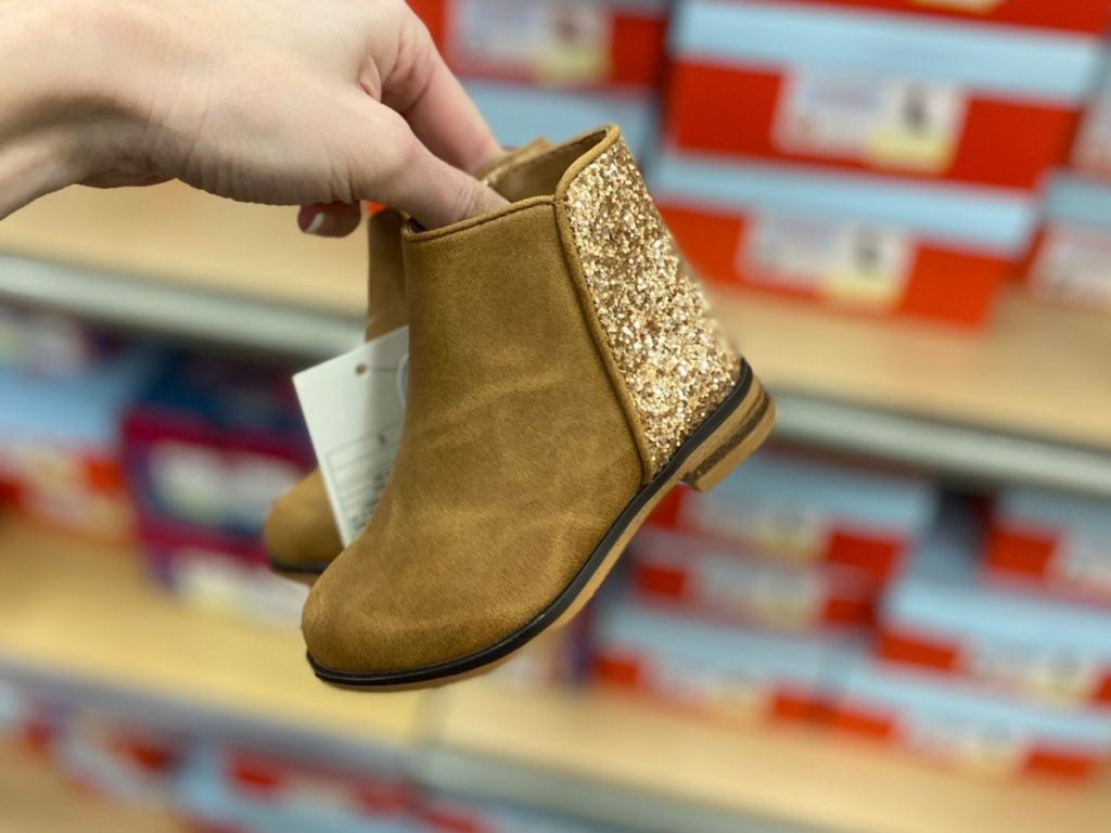 Hand holding Rona Toddler boots at Target