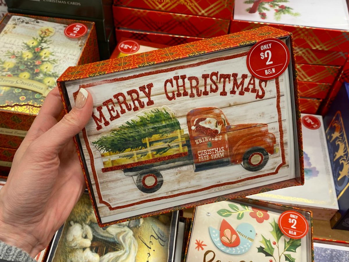hand holding box with Christmas card in it by store display