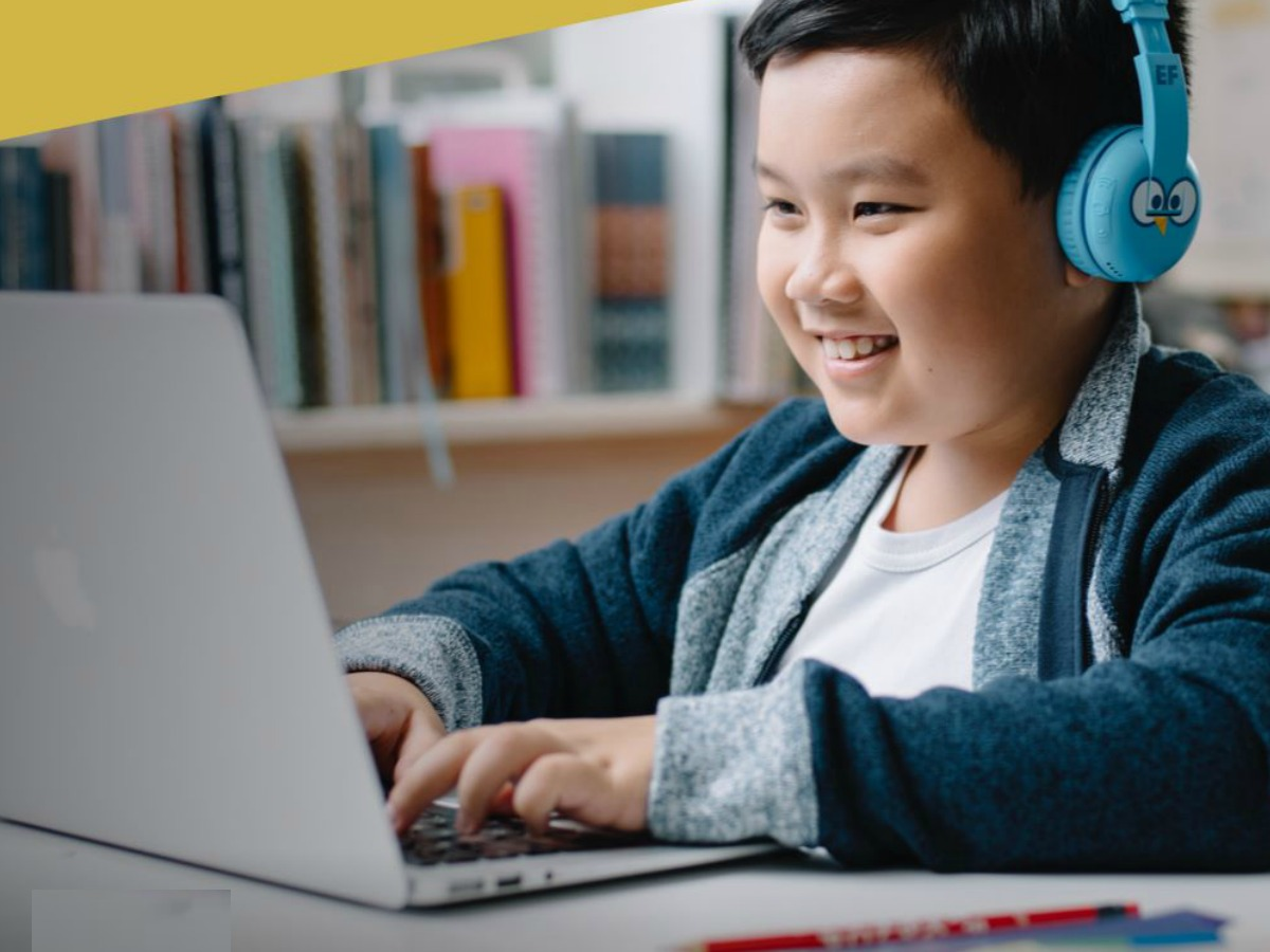 Boy wearing blue headphones and working on computer