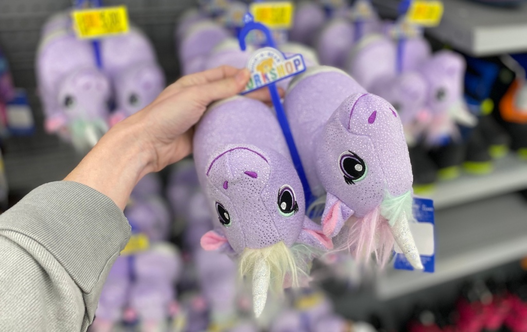 hand holding a pair of Build-A-Bear Unicorn Slippers upside down