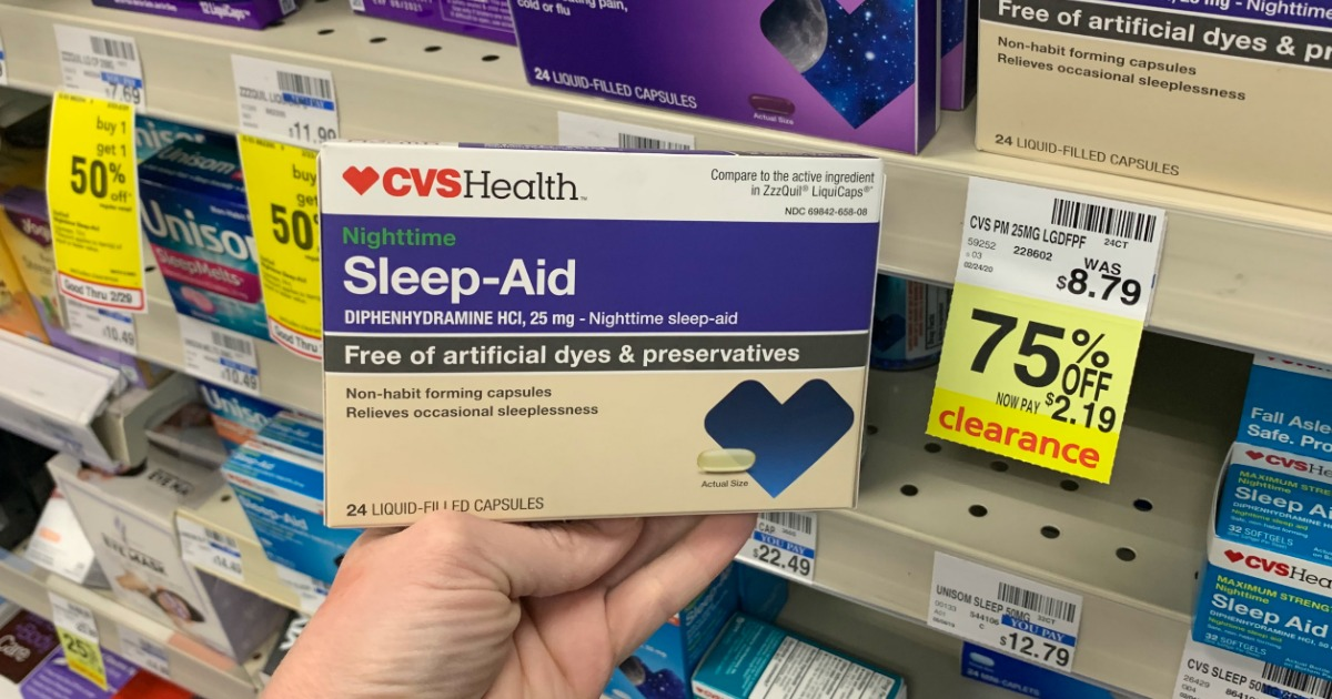 Hand holding sleep medicine in front of shelf
