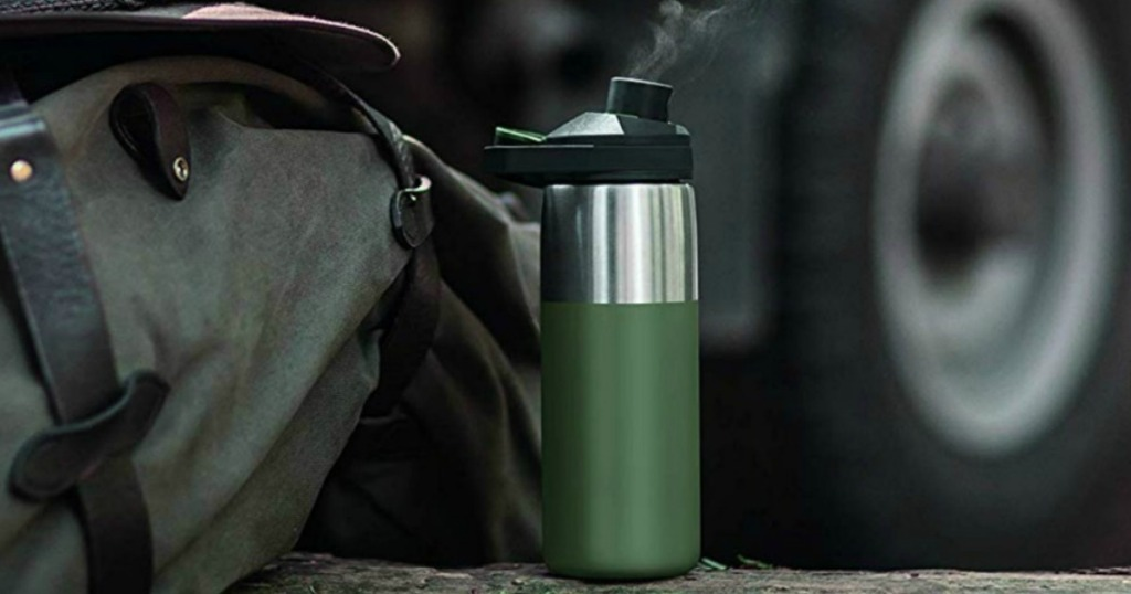 Large flask water bottle in olive green near bag and hat on ground