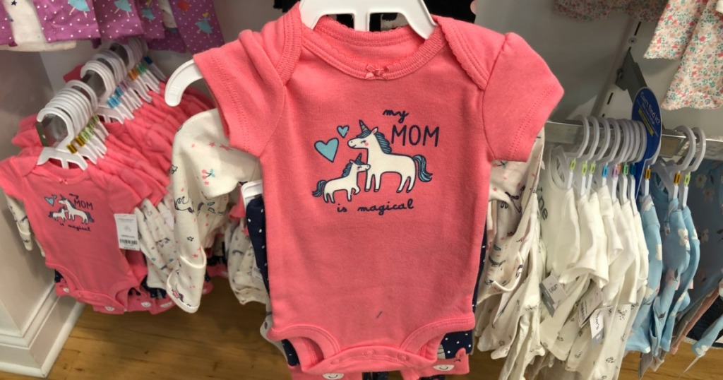 Carter's bodysuit with a unicorn on it on a hanger