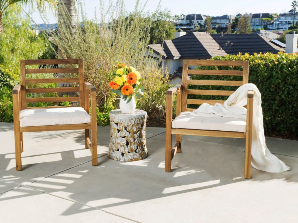 two wood chairs with white cushions outside on patio