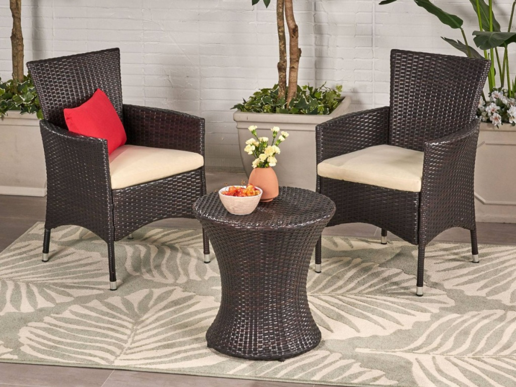 brown wicker 3pc patio set on white and gray leaf rug on patio