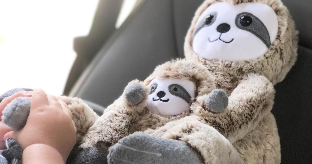 Baby holding two plush sloth toy animals