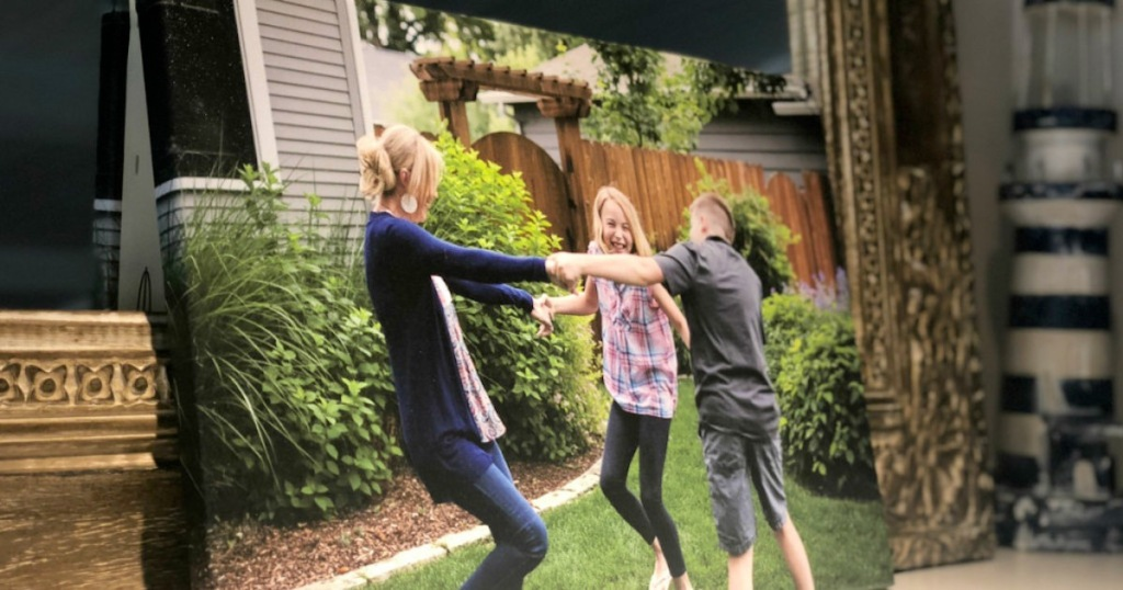 canvas photo print of mom with son and daughter holding hands playing on lawn