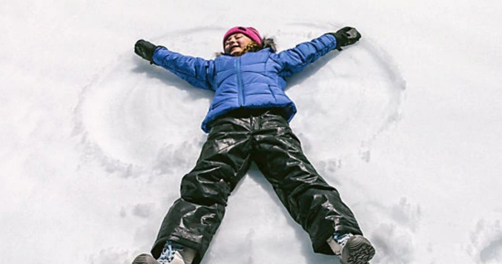 Girl wearing Columbia Coat making a snow angel