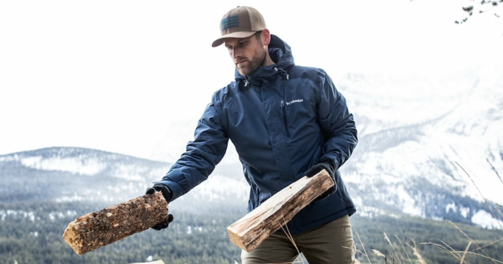 man outdoors wearing jacket and hat while handling firewood