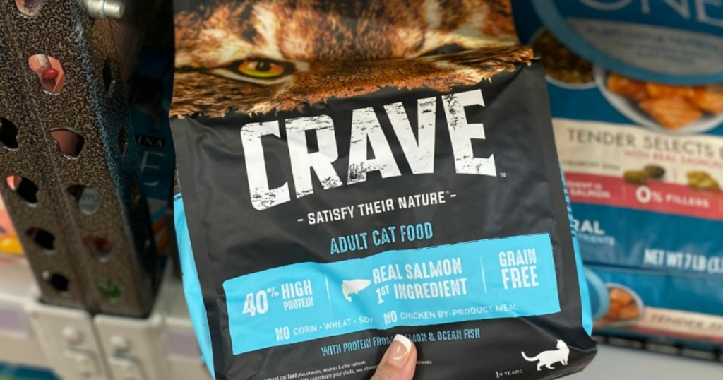 hand holding a bag of Crave Adult Cat food on shelf at the store