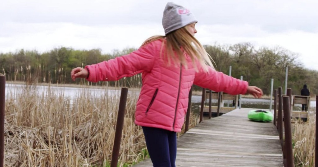 girl spinning on a dock wearing a pink jacket
