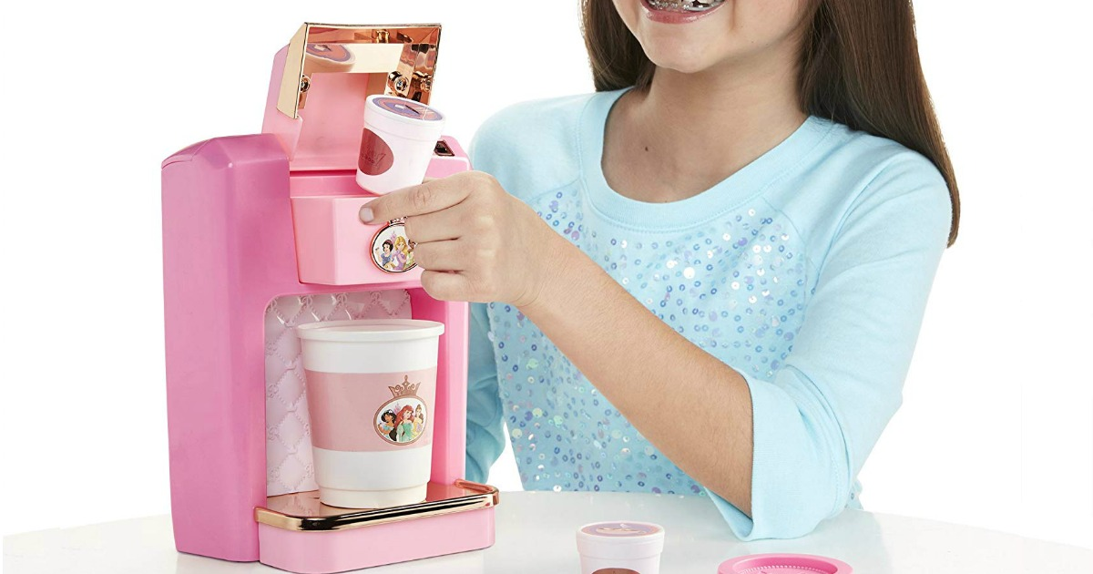 girl playing with a toy Disney Coffee Maker Set