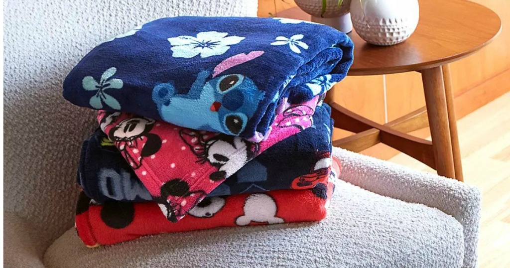 blankets with Disney characters on them folded and stacked