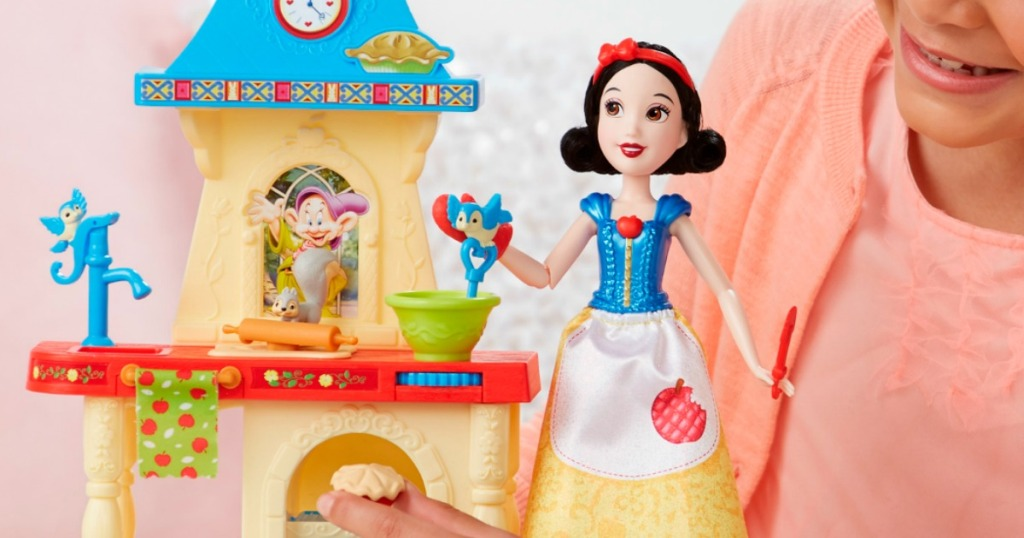 girl playing with snow white doll and playset