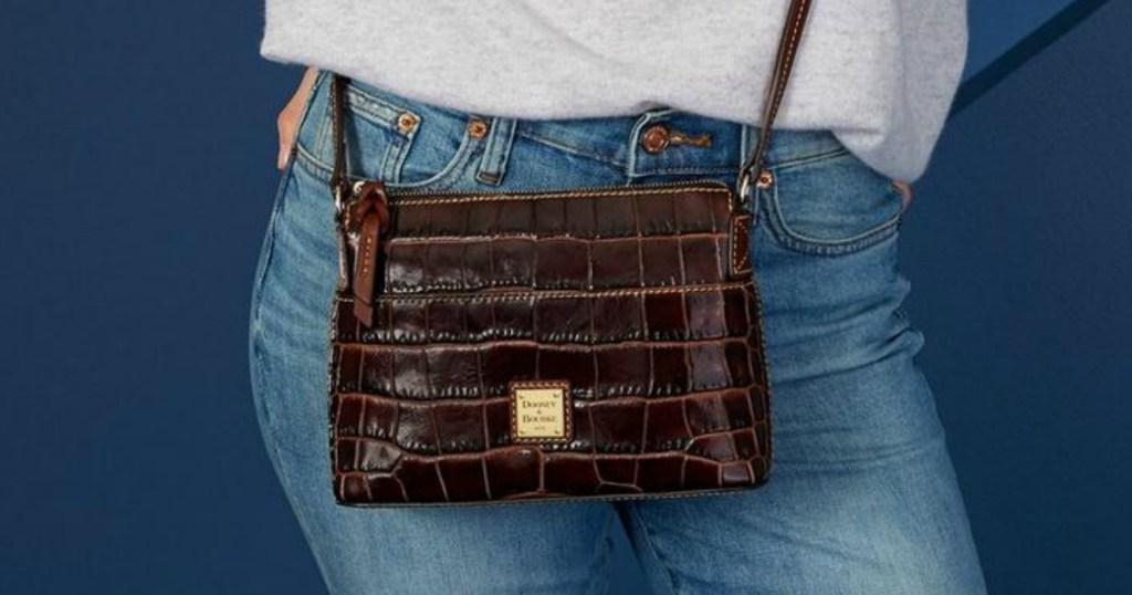 Woman wearing small crossbody Dooney & Bourke handbag