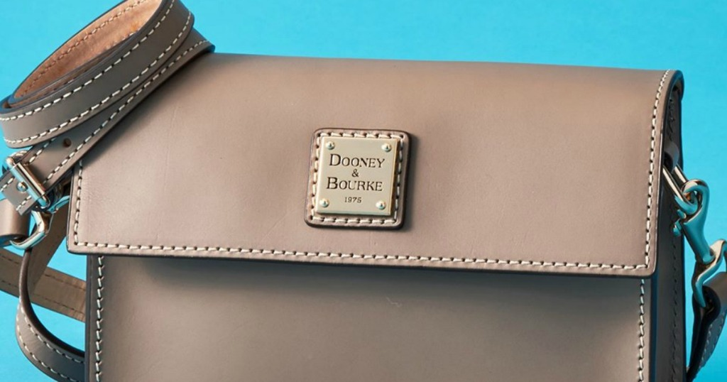 taupe Dooney & Bourke purse with a blue background