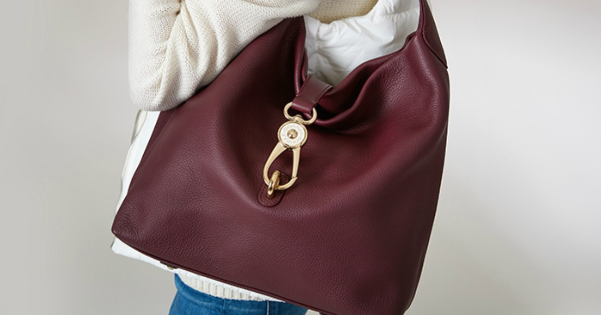 Woman wearing a large maroon tote-style slouch bag