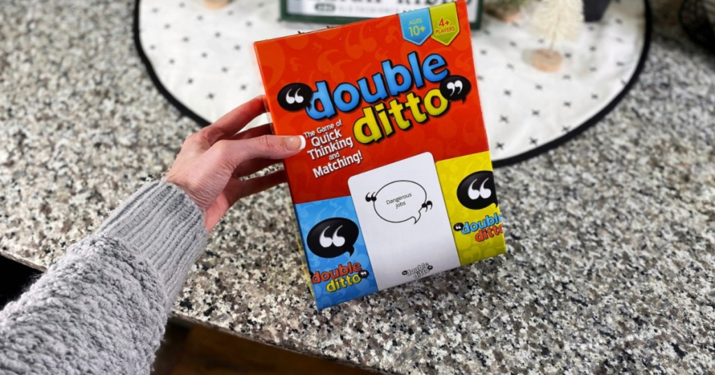 hand holding double ditto game with marble counter in background