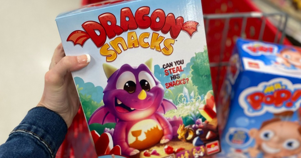 hand holding Dragon Snacks game box by Target cart