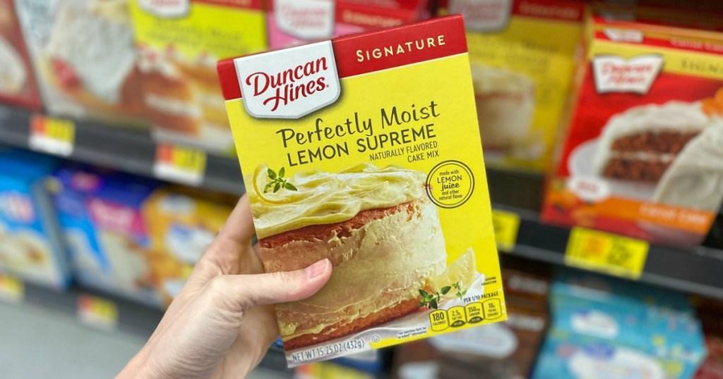 woman holding a box of lemon Duncan Hines cake mix