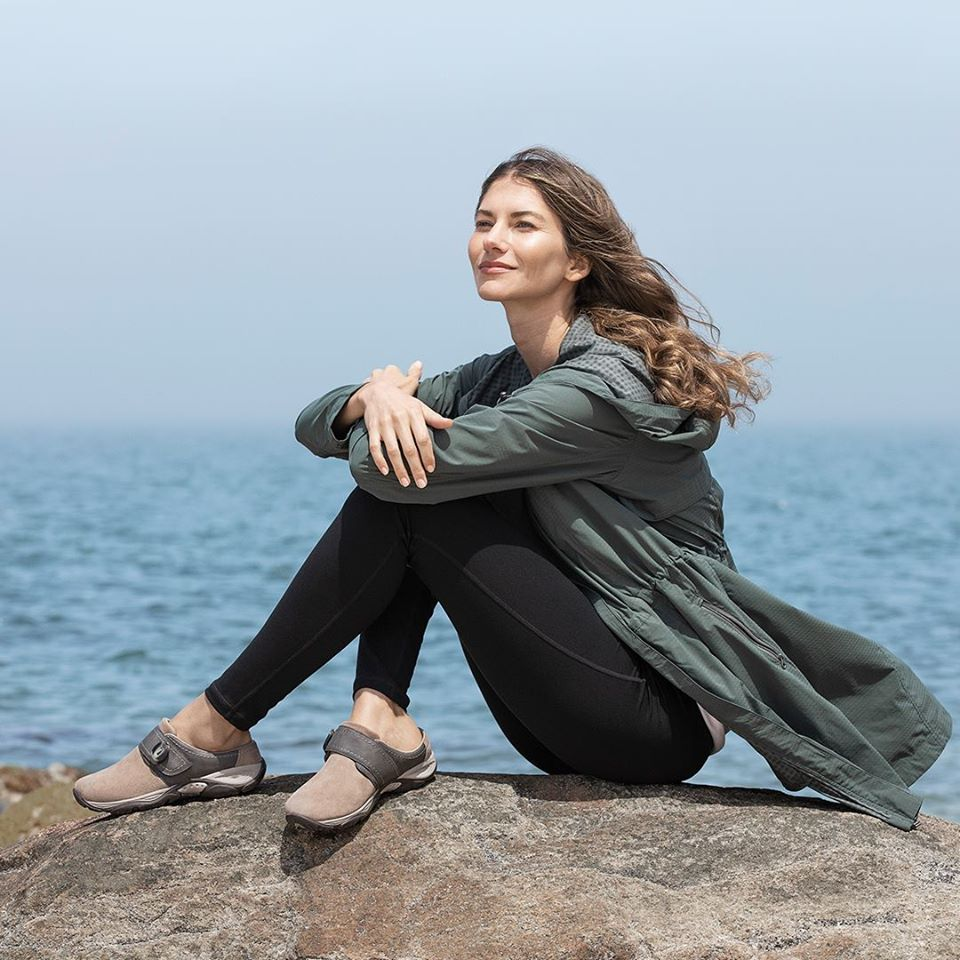 Woman sitting on stone overlooking water while wearing Easy Spirit Equip Shoes