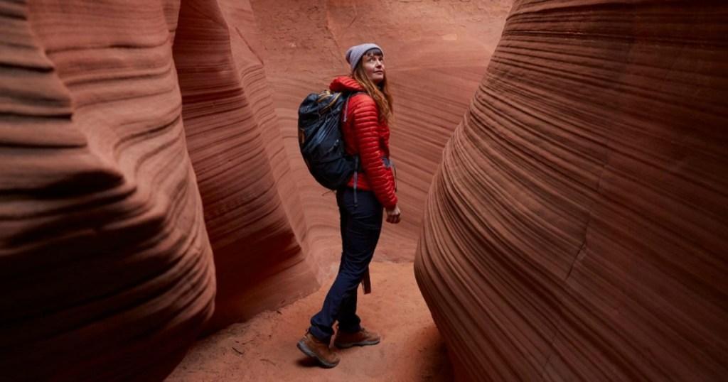 woman walking through a canyon wearing a backpack
