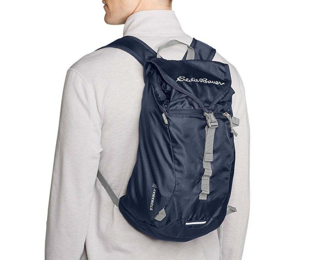 man wearing navy Eddie Bauer Stowaway Packable 20L Ruck Pack