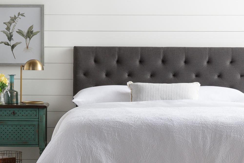bed with a charcoal headboard next to a nightstand