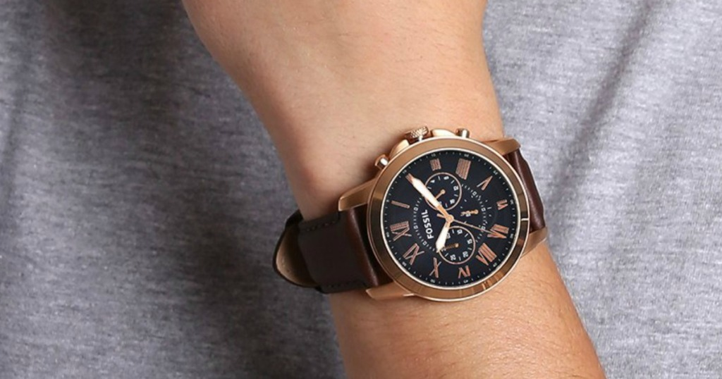 man in gray shirt wearing a rose gold Fossil watch