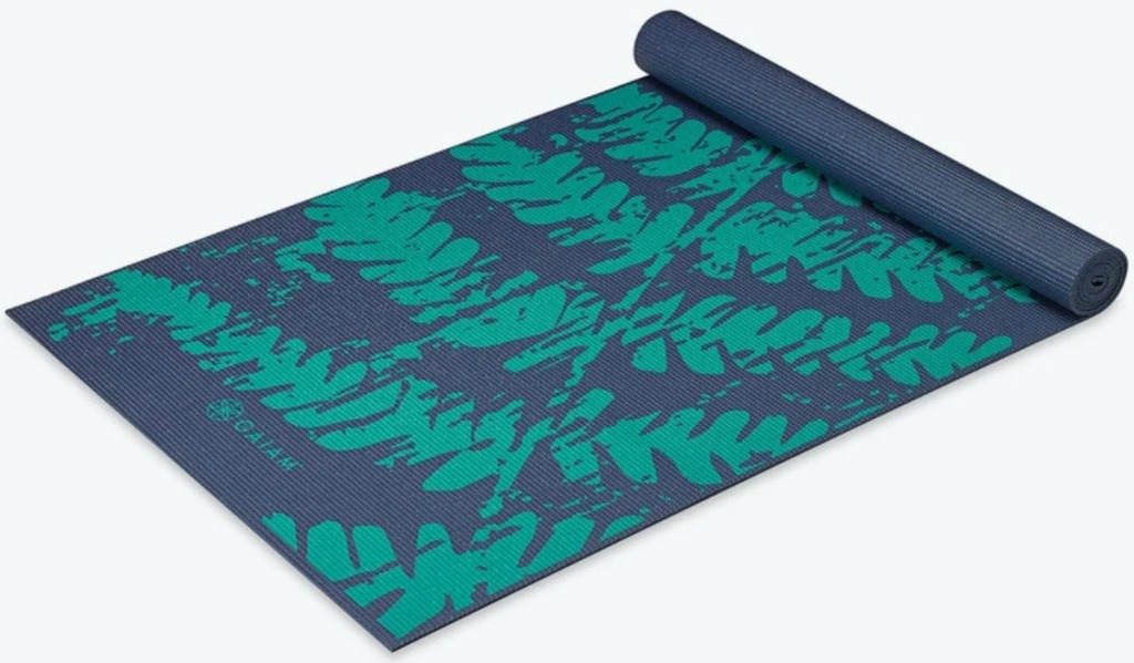 Navy blue yoga mat with green fern leaves print, partially rolled out